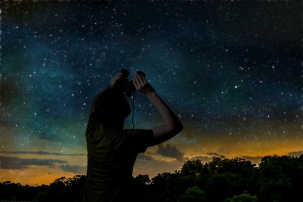 person looking up in the night sky with binoculars