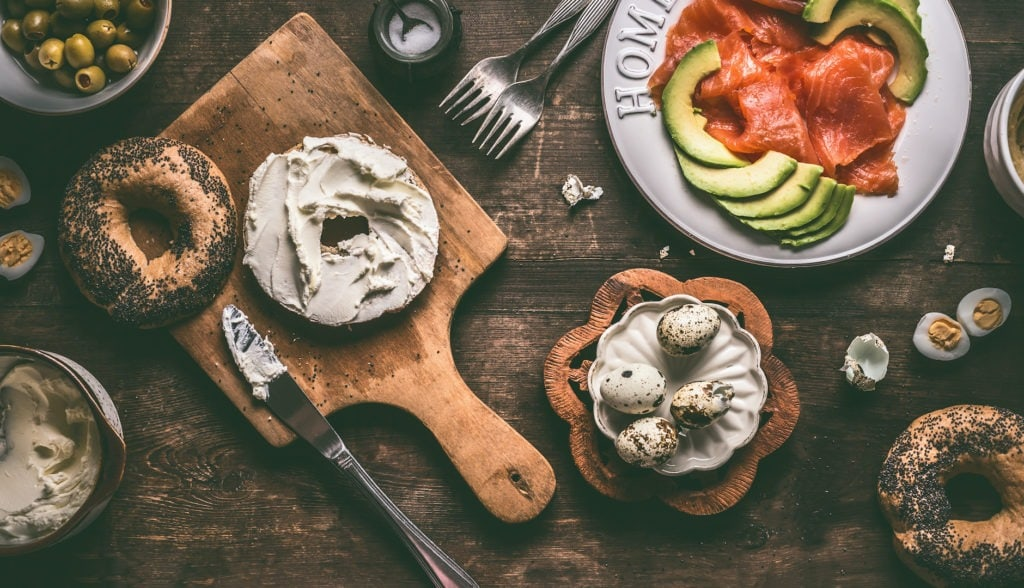 Bagel spread with cream-cheese on rustic breakfast table with ingredients: salmon, avocado, hummus and quail eggs.