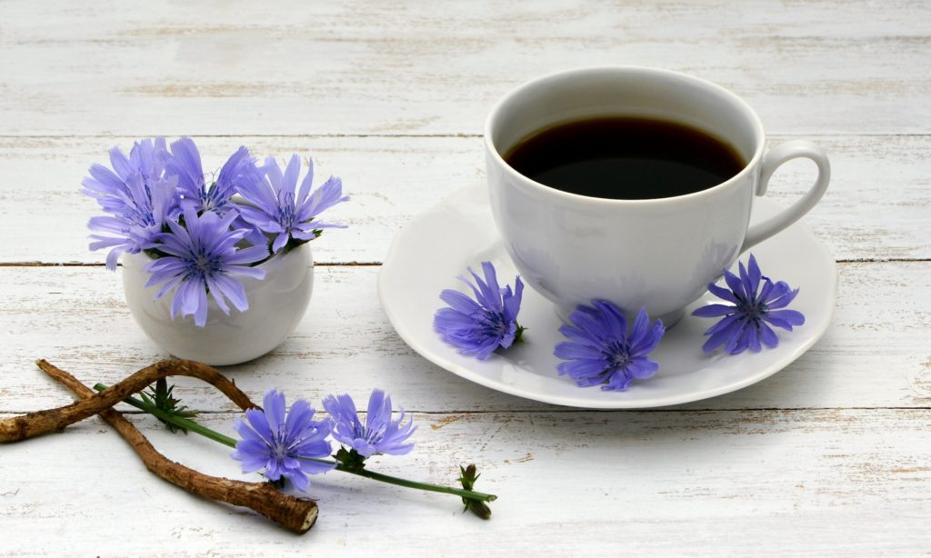 coffee cup with black coffee and purple flowers on plate