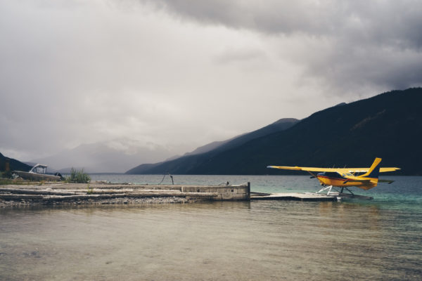 yellow planed docked at a pier with mountains and fog in Alaska