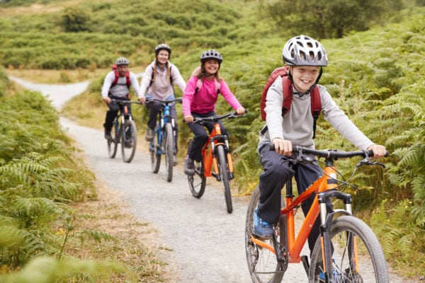 Family riding bikes together on a trail for Mother's Day