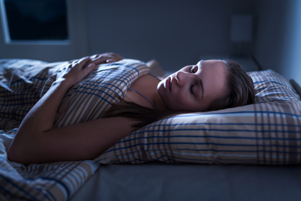 Calm and peaceful woman sleeping in bed in dark bedroom. Lady asleep at home in the middle of the night. Pillow, blanket and moonlight.