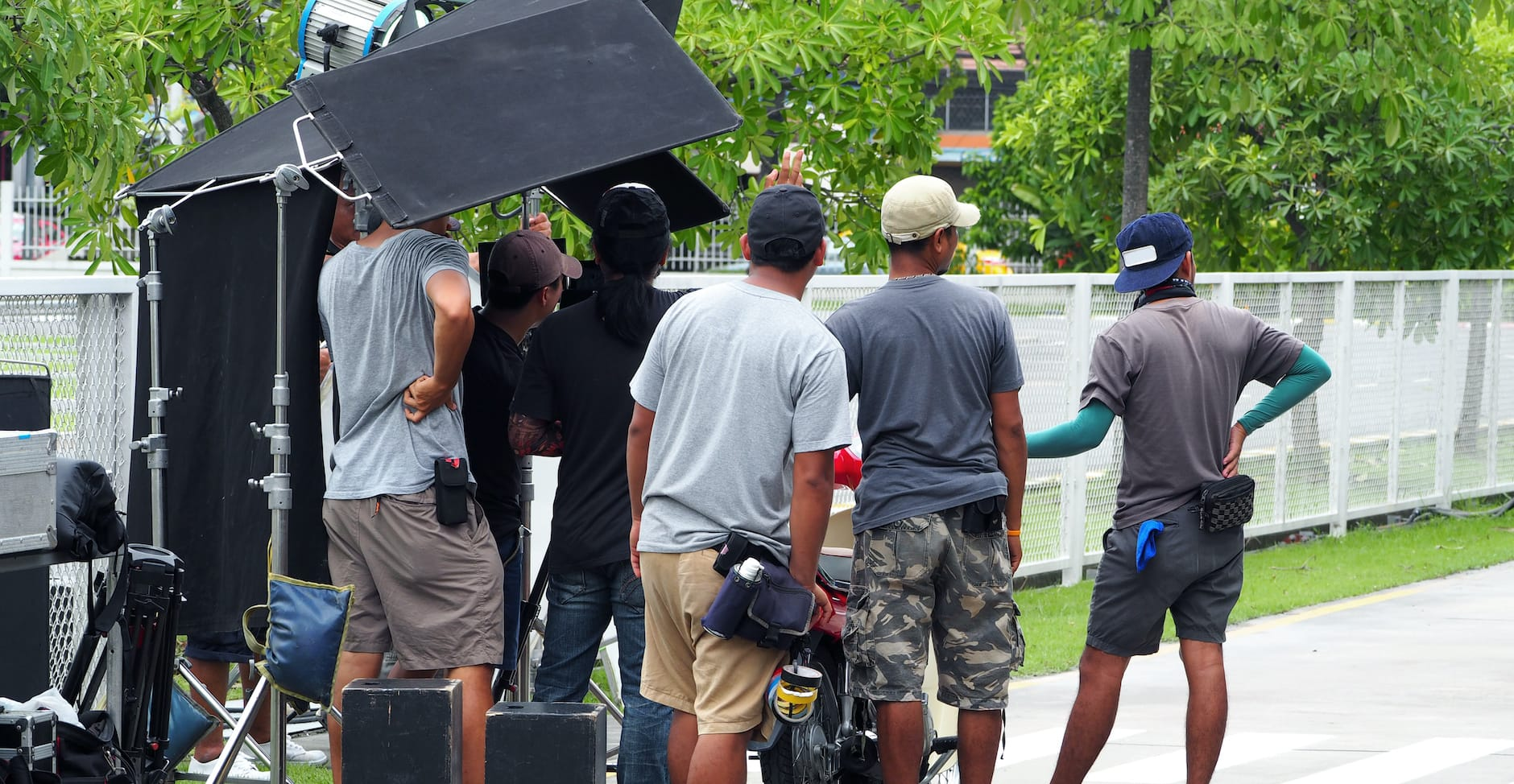 People filming on location in neighborhood.