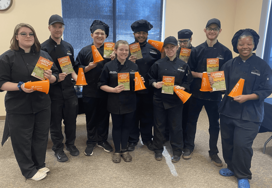 Chef students from the Green Ladle Culinary Arts School of Lewiston, Maine holding up copies of the Farmers' Almanac.