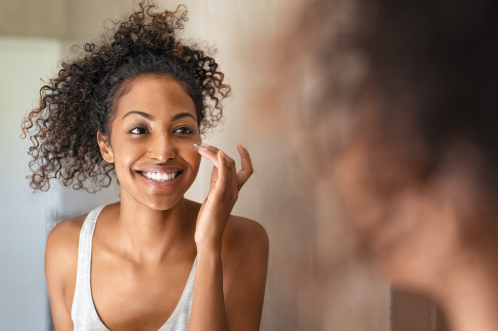 Young black woman applying moisturising cream to her skin while standing in front of the mirror in the bathroom. African american girl applying face cream while smiling. Beauty hydrating moisturizer and skincare routine concept.