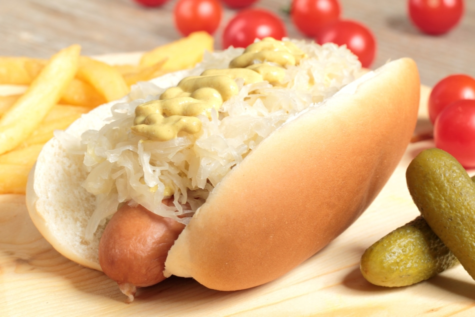 Hot Dog with sauerkraut and mustard toppings.