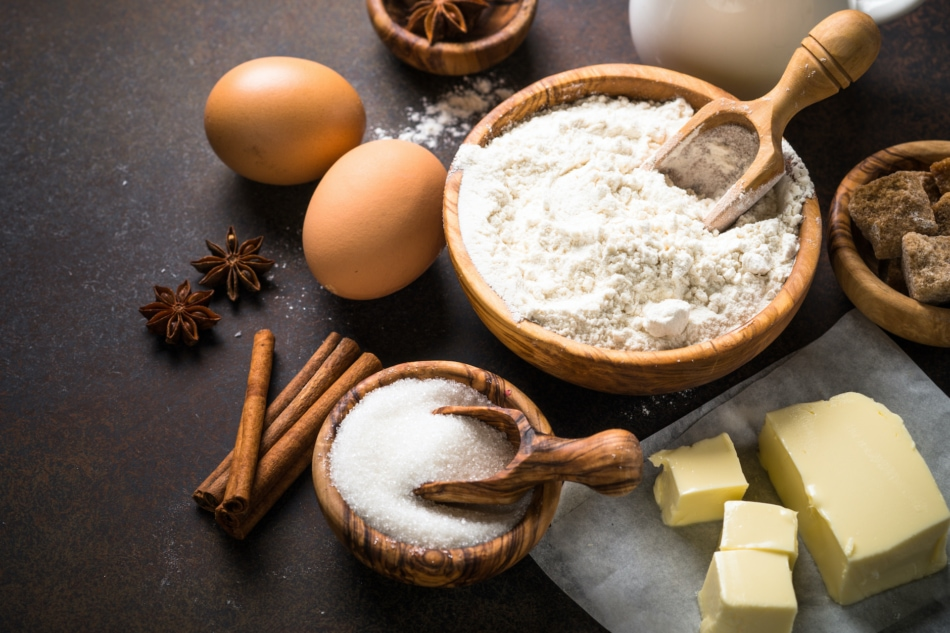 Arranged baking ingredients for cooking, including flour, eggs, butter, sugar, milk and spices.