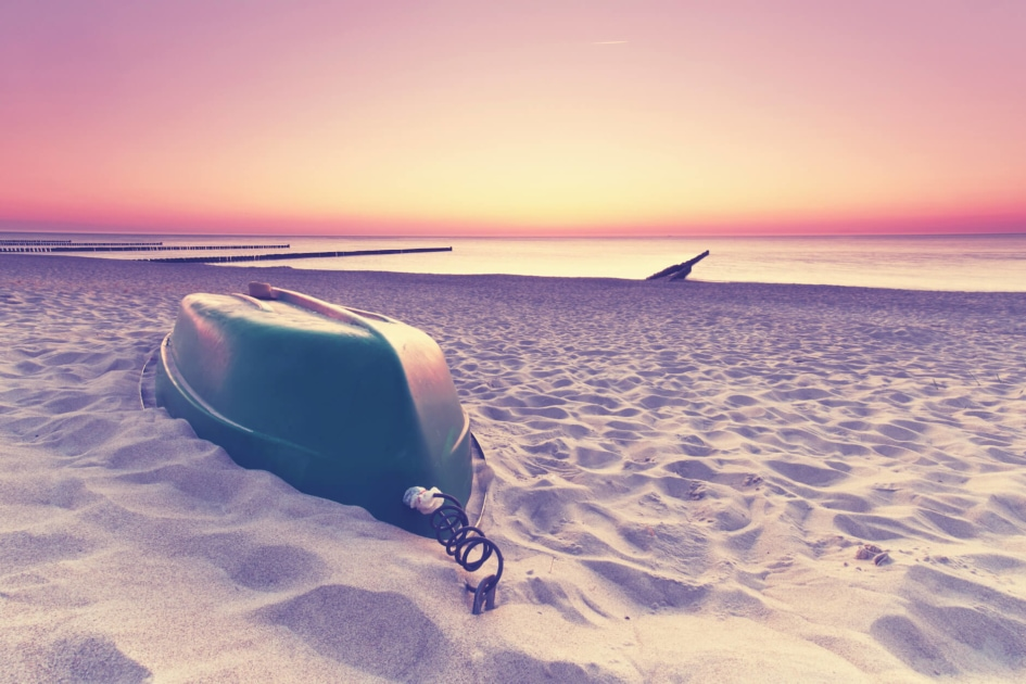 Rowboat stored upside down on a sandy white beach.