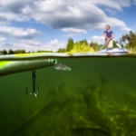 green fishing lure in green water with fisherman