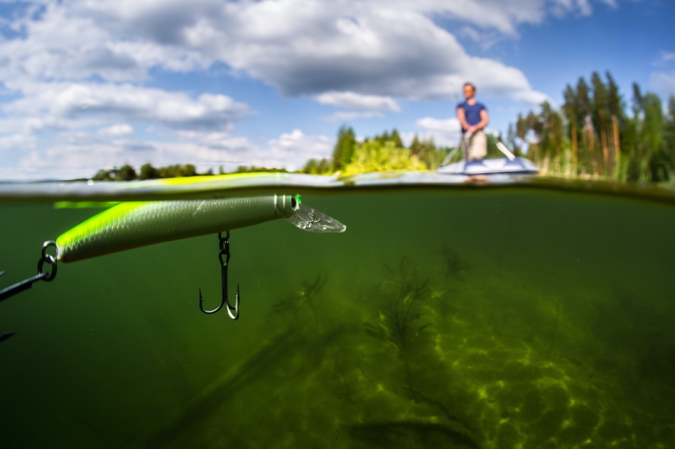 Fishing lure shown up close and under water with fisherman on boat in background.