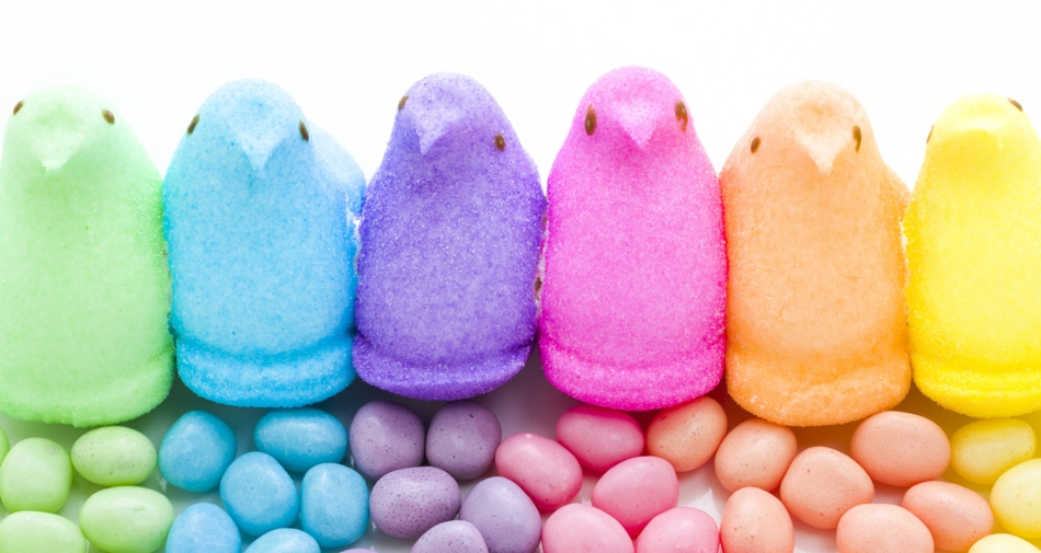 A variety of different colored marshmallow peeps with similarly colored jelly beans.