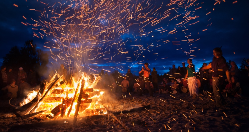 Group of people dancing in front of a bonfire on a beach at night.