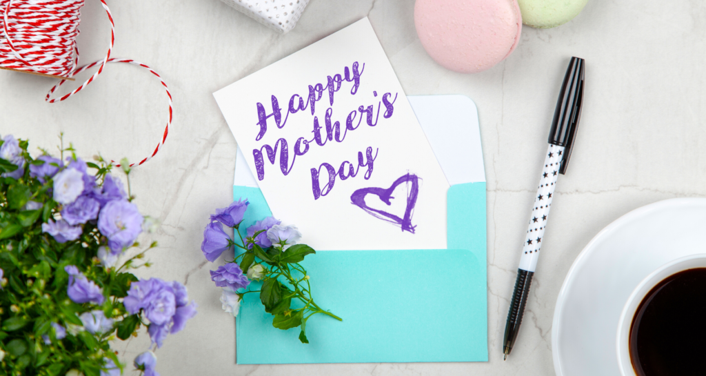 handmade Mother's Day card next to flowers, coffee, and macarons