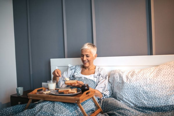 Mom with short gray hair enjoying mother's day breakfast in bed with toast and coffee