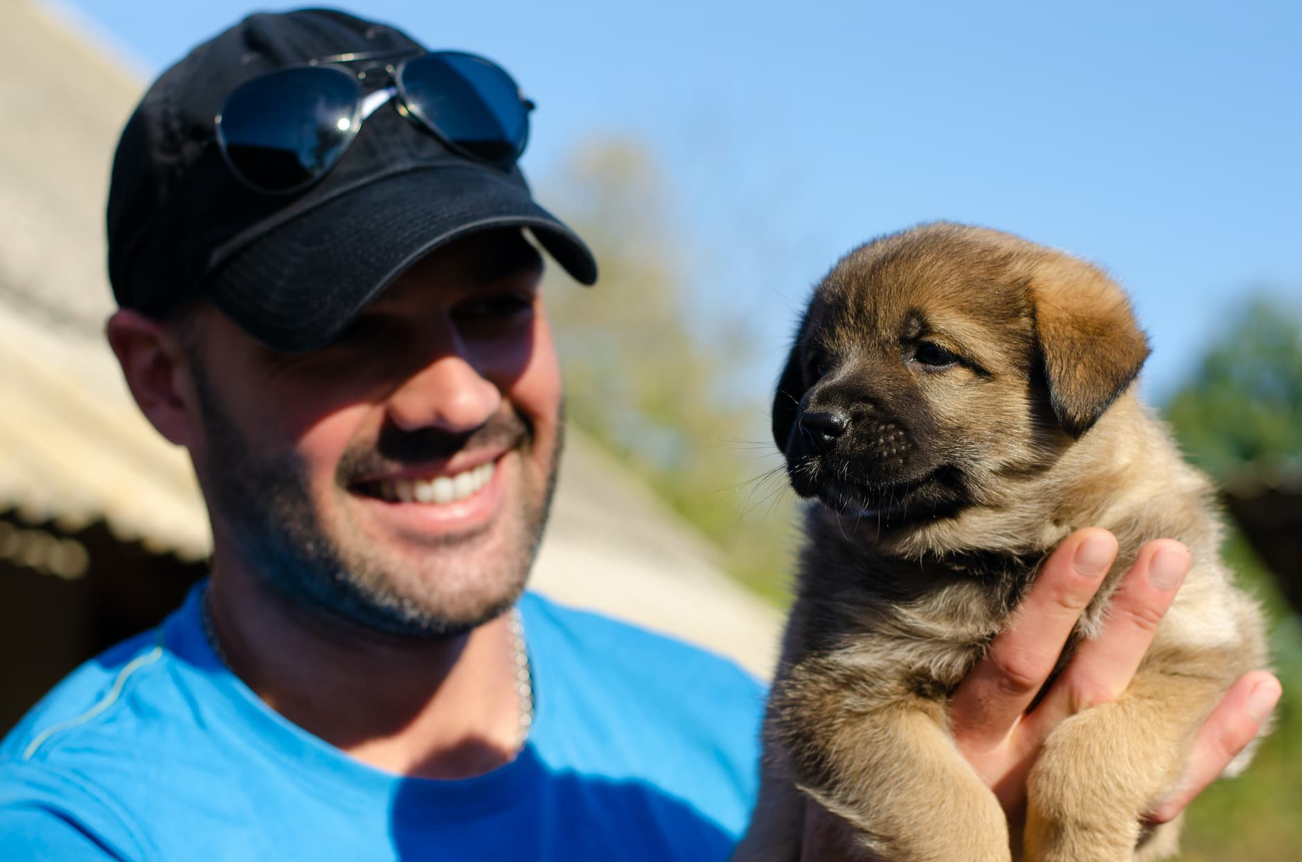 man wearing black baseball cap smiling and holding up a puppy