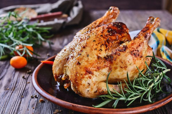 Delicious, freshly baked, crispy, baked chicken is appetizing served on a ceramic dish next to a sprig of fragrant rosemary