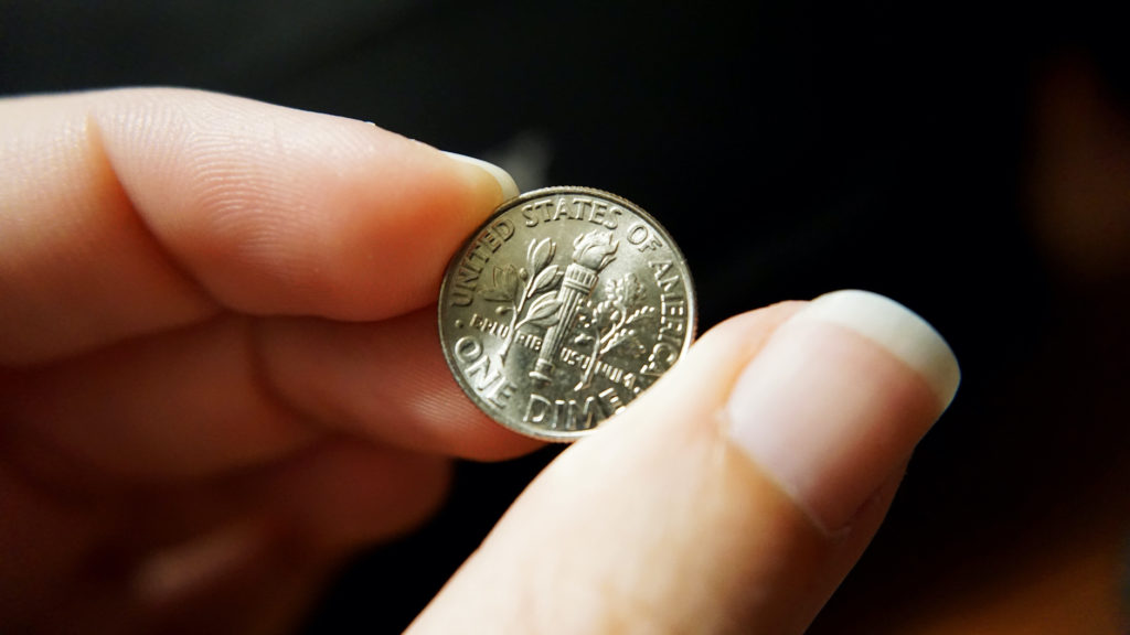 female hand holding up tail end of a dime