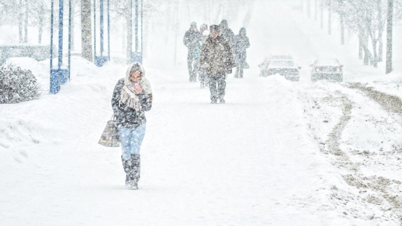 Young girl walks through a blizzard.