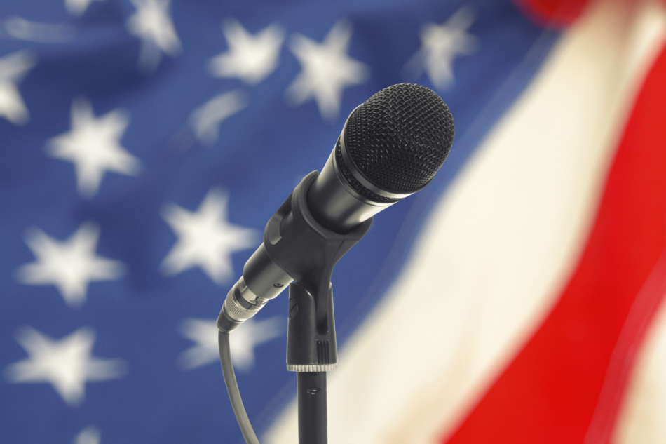 Microphone on stand with US flag on background.