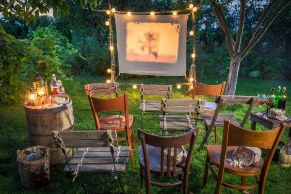 backyard movie viewing with a screen, lights and wooden chairs