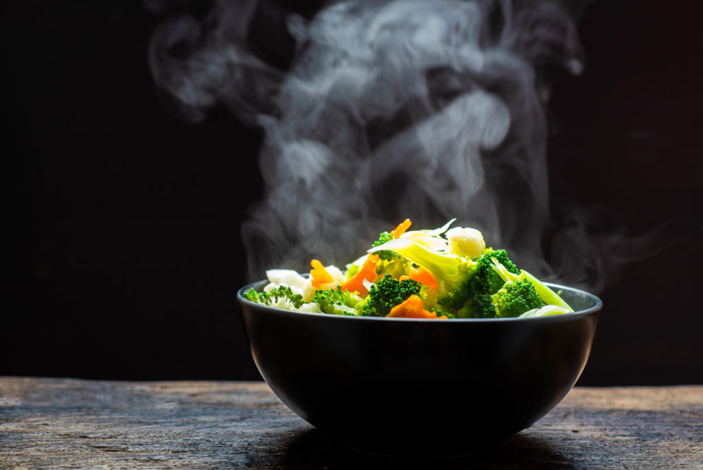 The steam from the vegetables carrot broccoli cauliflower on black bowl , a steaming. Boiled hot Healthy food on table on black background,hot food and healthy meal concept