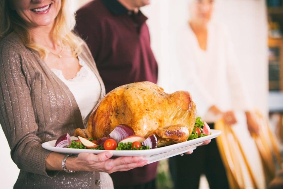 Woman holding a Thanksgiving turkey dish.