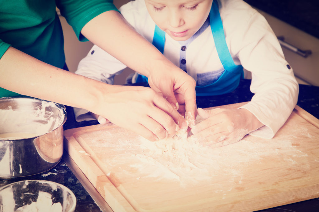 hands of mother and son kneading dough on wooden table