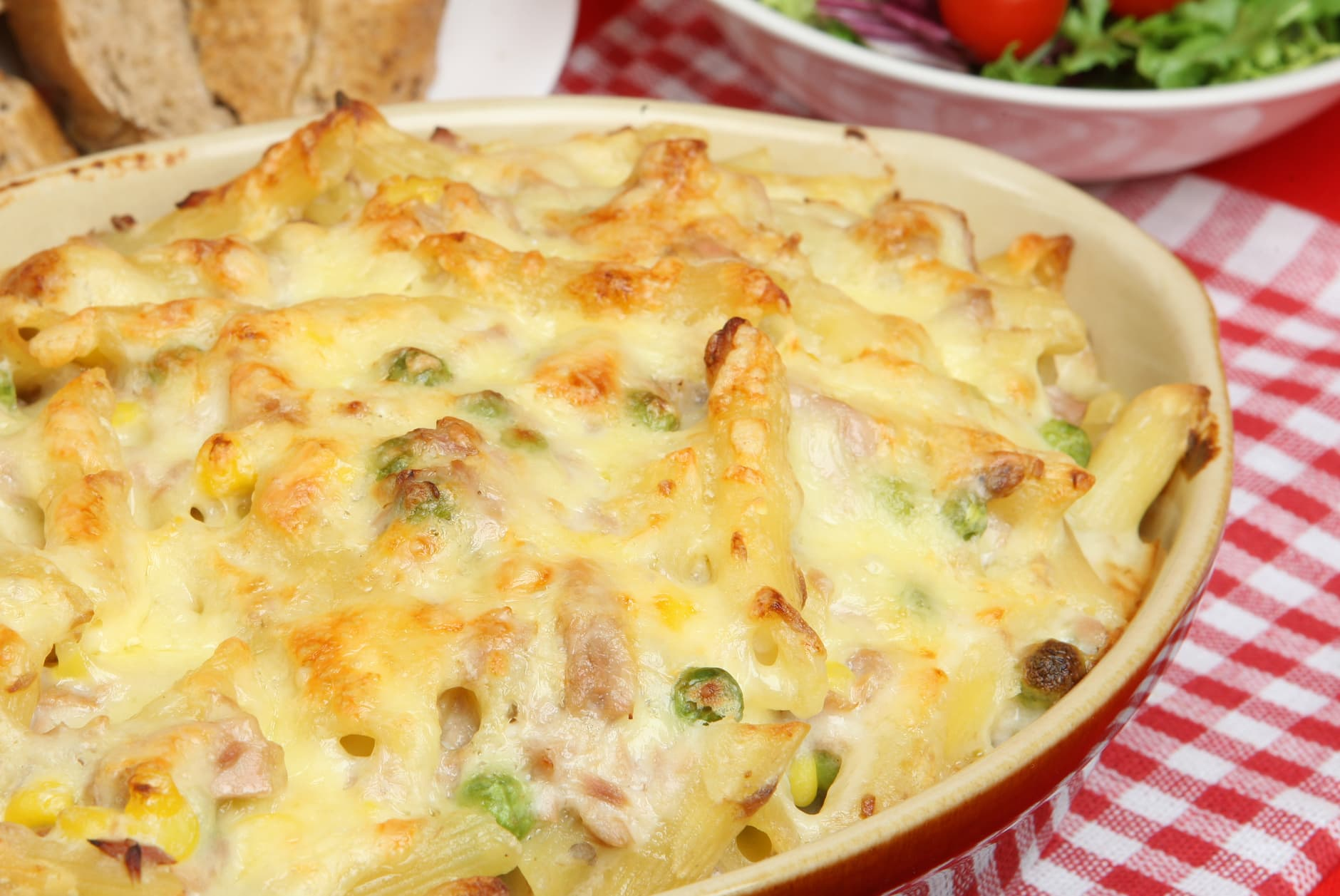 Tuna and pasta casserole on a table covered in melted cheese