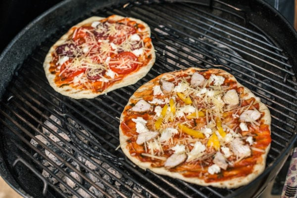 two pizzas on a charcoal grill