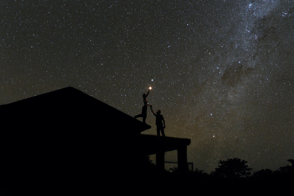 Couple shining flashlight at Milky Way from a rooftop.