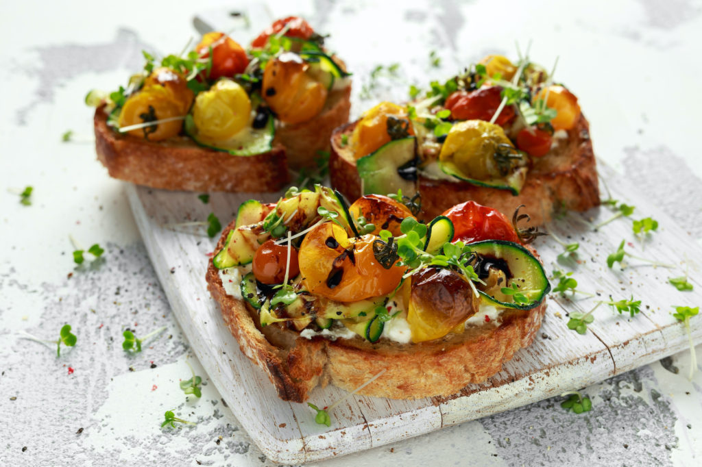 Healthy toasts with baked sweet cherry tomatoes and grilled zucchinin ribbons drizzled with balsamic vinegar.