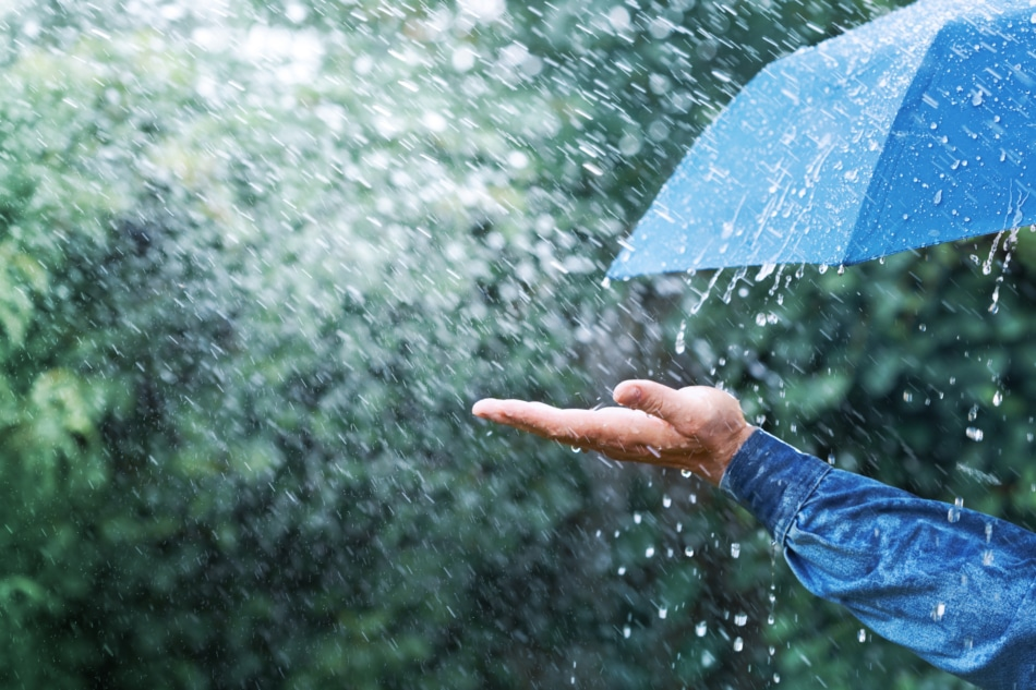 Man holding his hand out in the rain under umbrella. Climate and Weather concept.