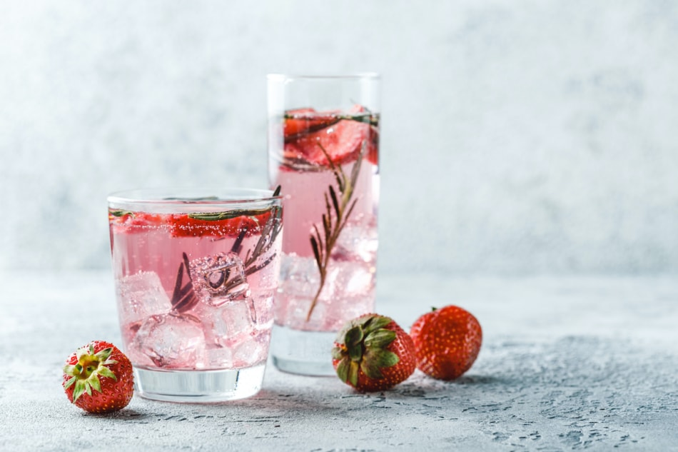 cocktail with strawberry tops and rosemary and ice in glass glasses.