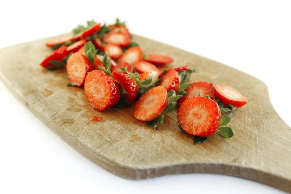 Strawberry tops on a wooden cutting board