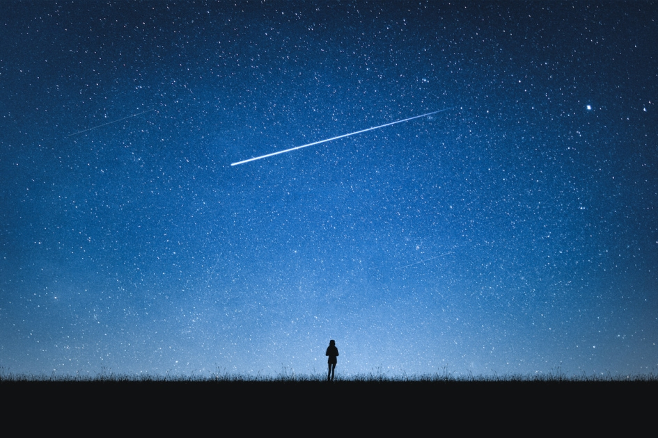 Silhouette of girl standing on mountain and night sky with shooting star.