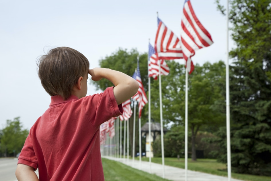 A young boy salutes the flags of a Memorial Day display along a small town street.