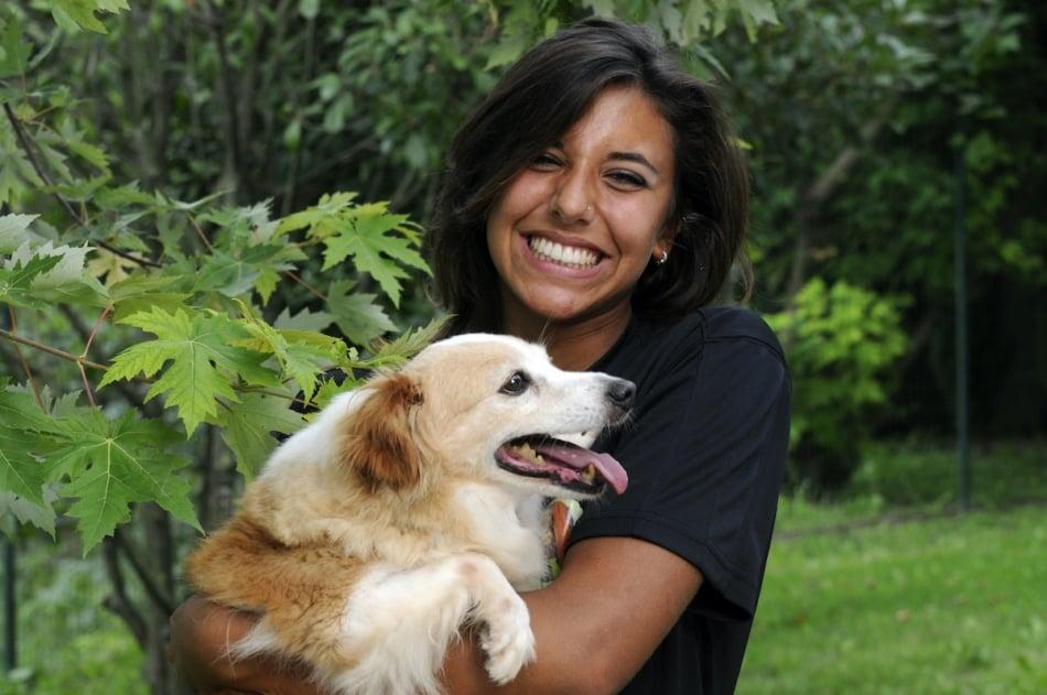 happy woman holding pet dog in garden