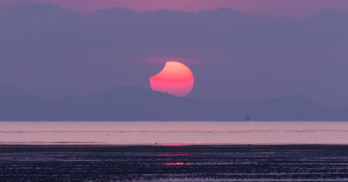 sunrise solar eclipse over the ocean