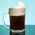 Root beer float in a mug on blue background.