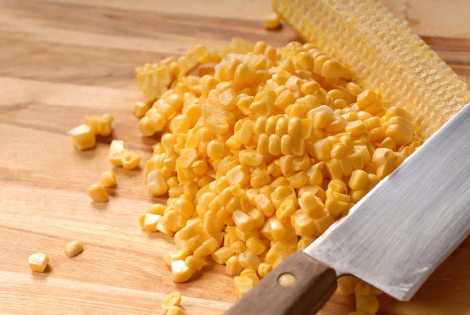 Corn kernels cut off the cob with a sharp knife on a cutting board.