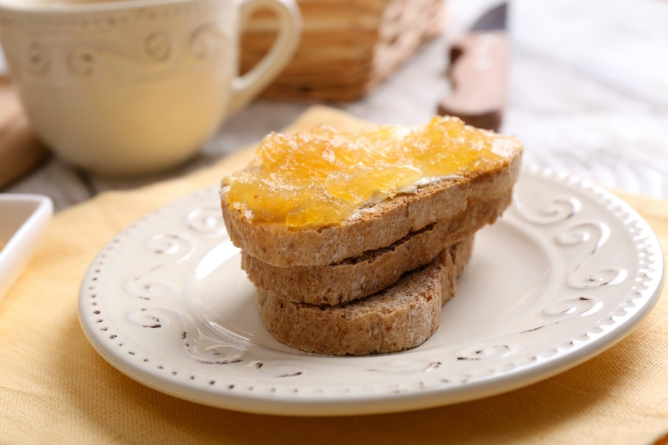 Fresh toast with butter and corncob jelly on table close up