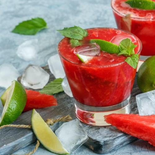 Glasses of watermelon mojito, slices of lime, mint and ice on the serving board.