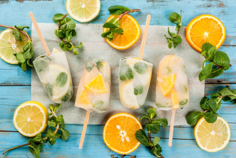 Frozen mojito mocktail ice pops with mint sprigs and lemon slices.