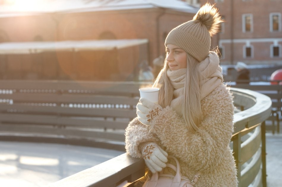 Woman bundled up in the cold with steaming coffee.