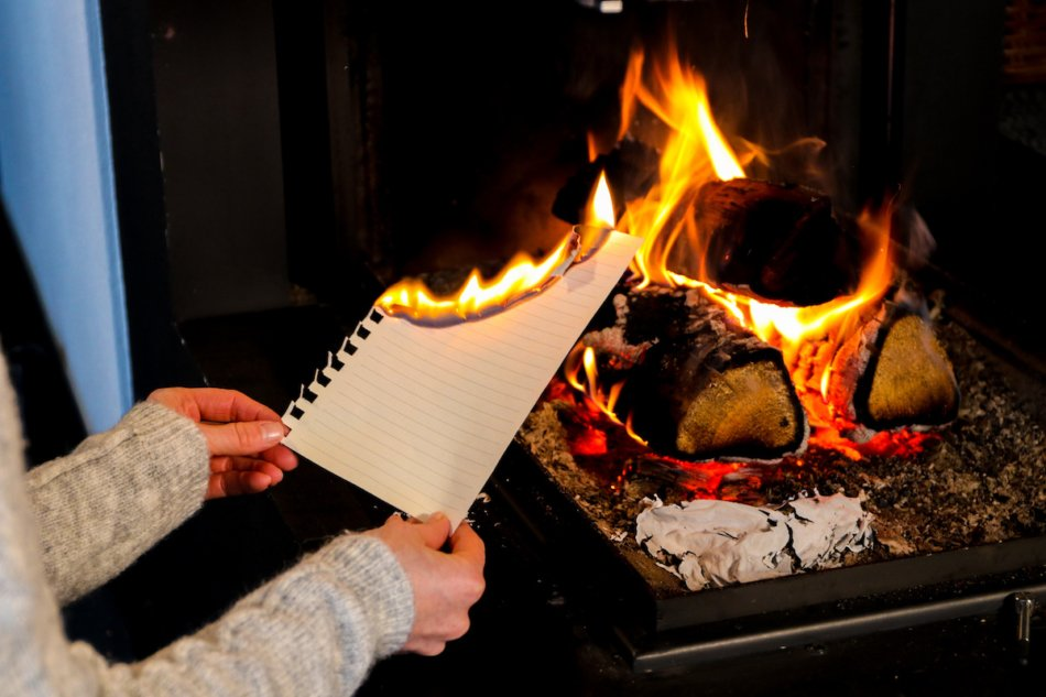 woman burning letter in fireplace.