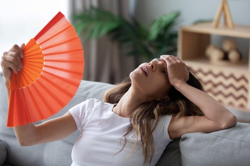 overheated woman fanning herself with an orange fan.
