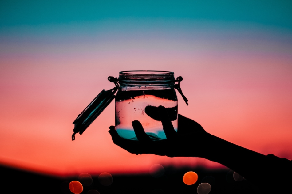 The silhouette of a person holding a jar of water during a beautiful sunset with a blurred background and bokeh lights.