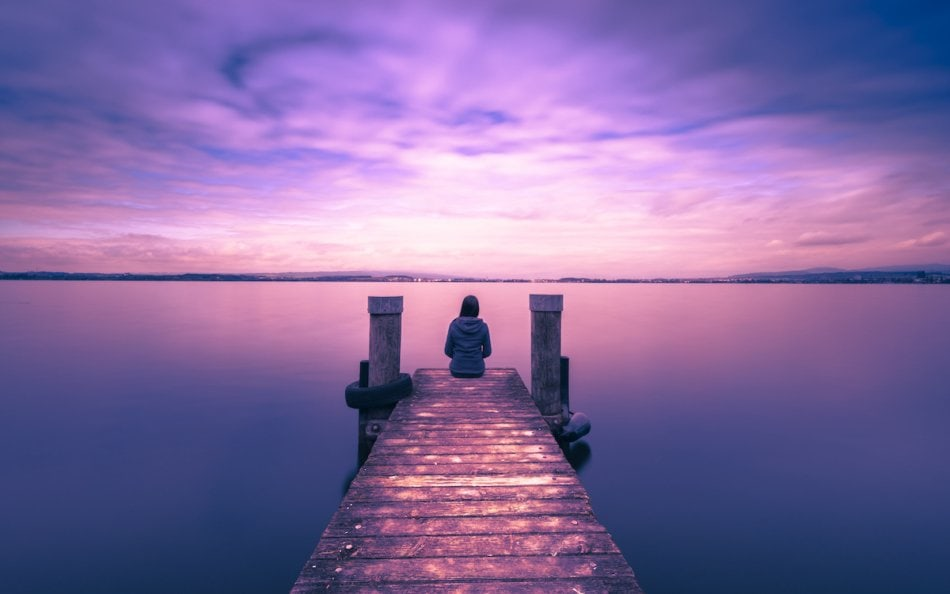 One woman sits on a wooden pier. Cloudy above the lake.
