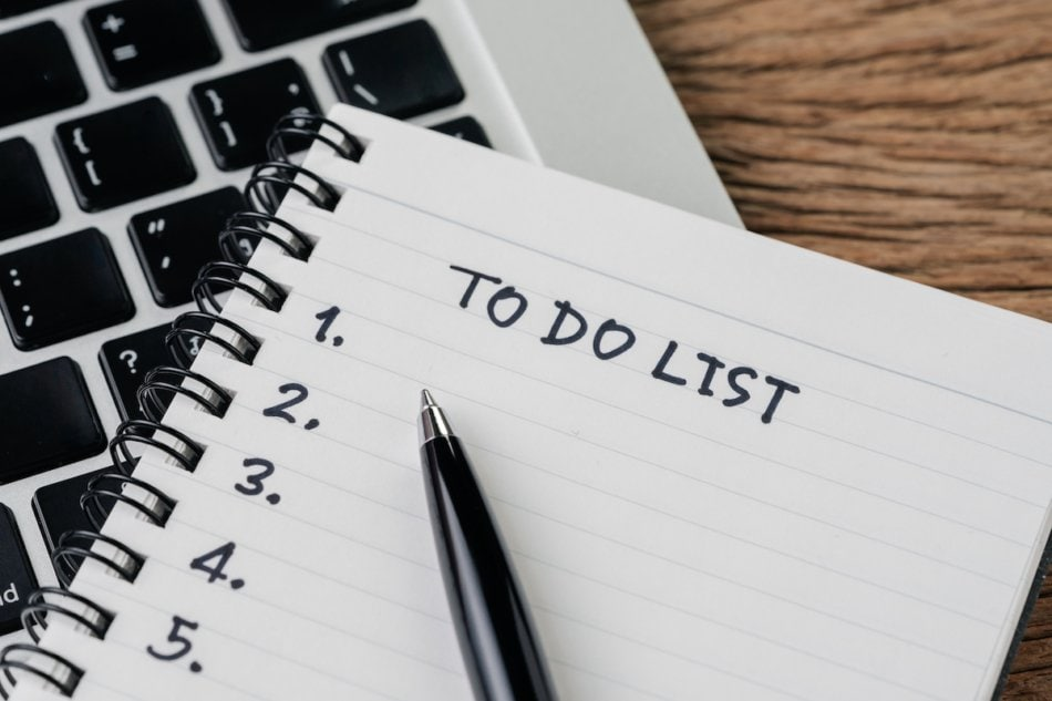 To do list, checklist of things or tasks to complete for life habit, business project plan concept, black pen on notepad with headline To do list and list of numbers on computer laptop, wooden table.