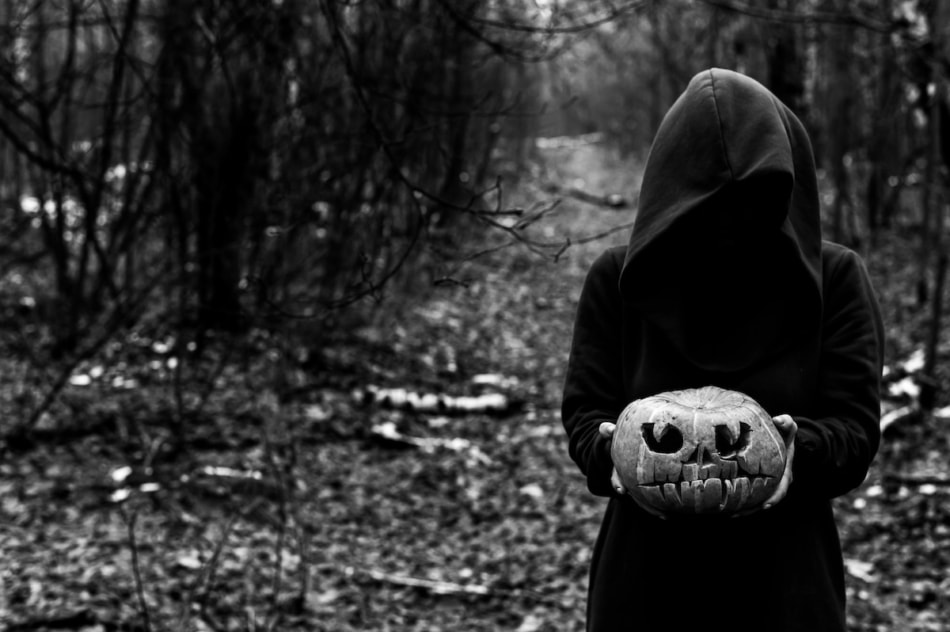 A witch holds a creepy pumpkin in a dense autumn forest. Jack o lantern for halloween. Monochrome.